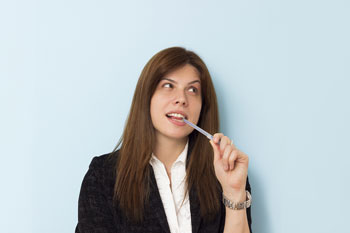 Business woman biting on pen