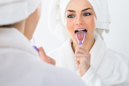 Woman using tongue scraper