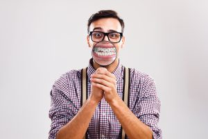Man magnifying teeth and braces