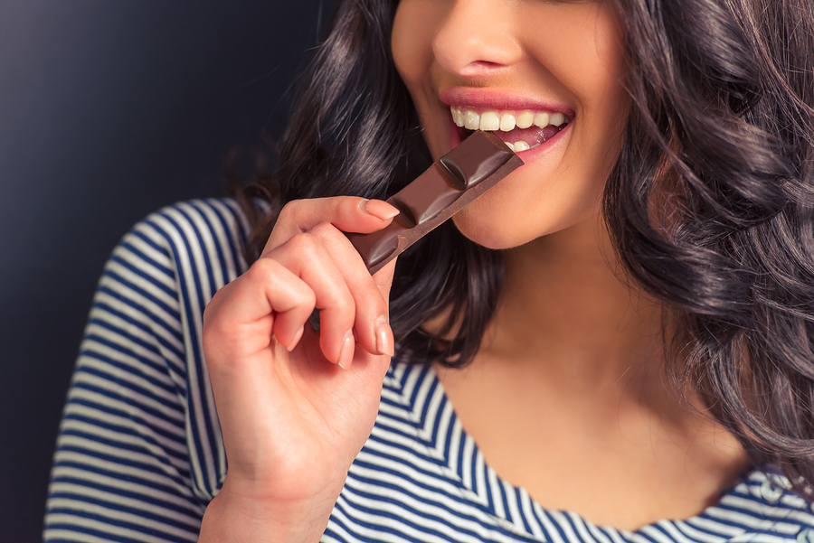 Woman smiling and eating chocolate